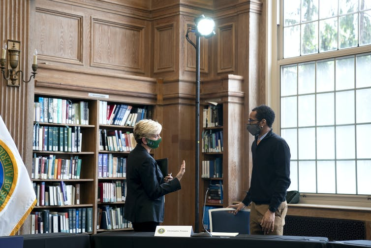 A masked woman and man speak under a spotlight in a booklined room