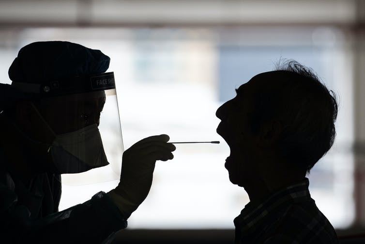 Man in shadow opens mouth to get COVID test.