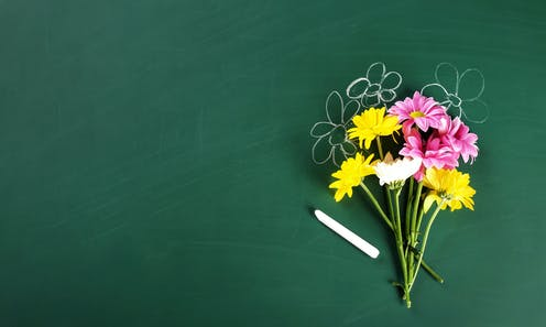 A boquet of flowers in front of a chalkboard with chalk flowers drawn behind them.