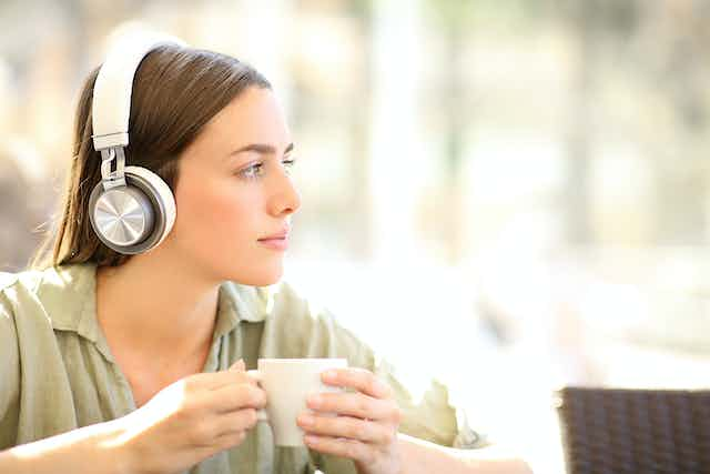 Young women with headphones on listens pensively