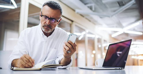 middle-aged man with phone and laptop making notes