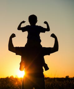 Father with son on his shoulders with both flexing their muscles.