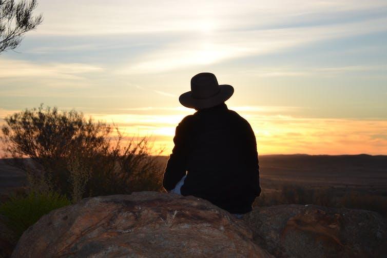 farmer sits on rock