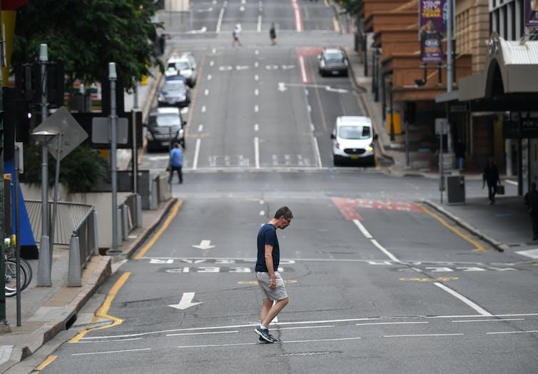 Man crosses an almost deserted city street
