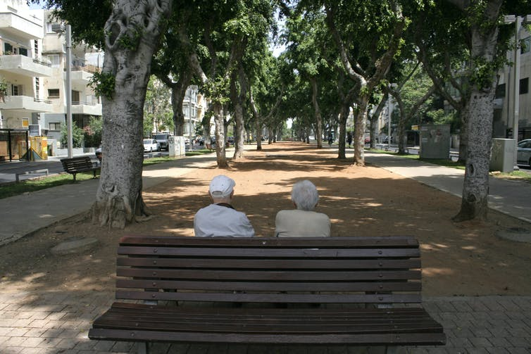 Elderly couple sit on a bench in shade under street trees