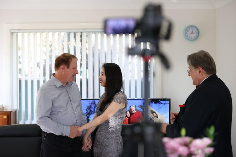 Couple in grey plain clothes get married on camera in their living room as celebrant watches on