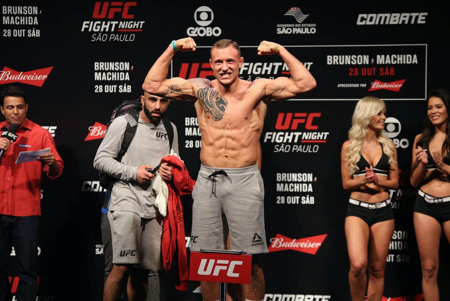A fighter flexes his biceps during a UFC weigh-in.