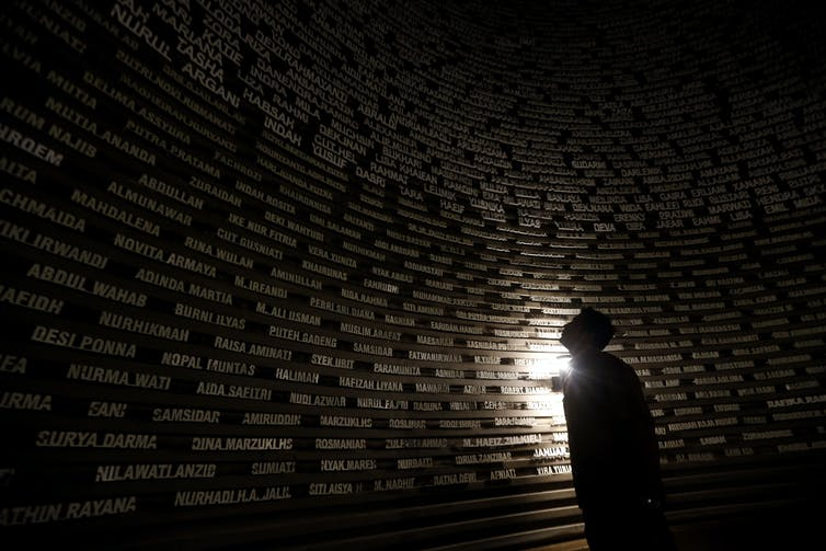 A man gazes at a wall of names in a dark room