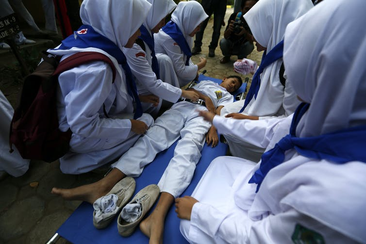 Schoolchildren in white outfits cluster around a young boy pretending to be injured.