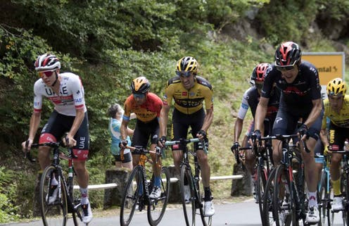 Racers in the Tour de France struggling up a hill.