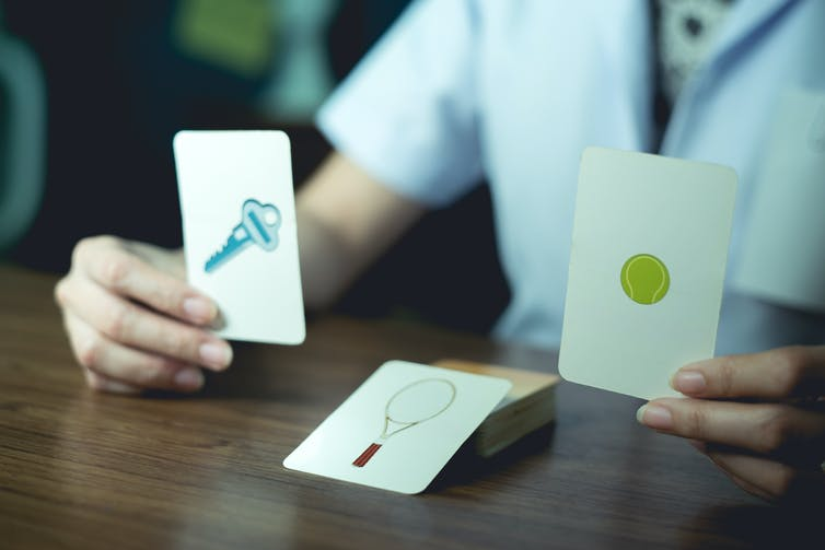 Un professionnel de la santé présente des cartes avec des images d'objets à un patient