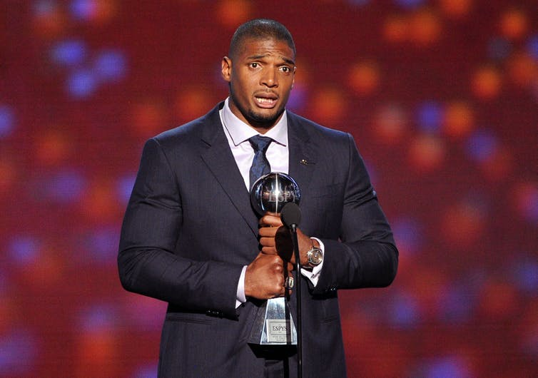 Michael Sam clutches his award as he speaks during the ESPYs.