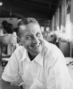 A clean-cut man in a white shirt smiles at the camera