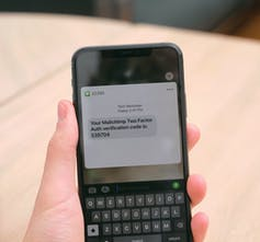 A hand holds a smartphone showing a text message on the screen