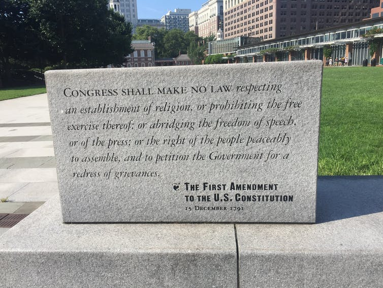 A stone carved with the text of the First Amendment