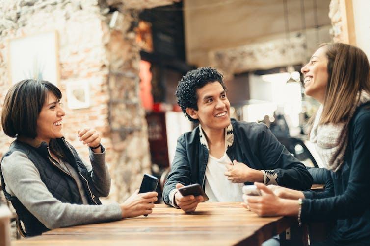 Tres personas se sientan en una mesa y hablan.