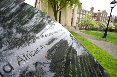 Words engraved on a stone plinth form a component of the Slavery Memorial by sculptor Martin Puryear, erected in 2014, on the Brown University campus in Providence, R.I.
