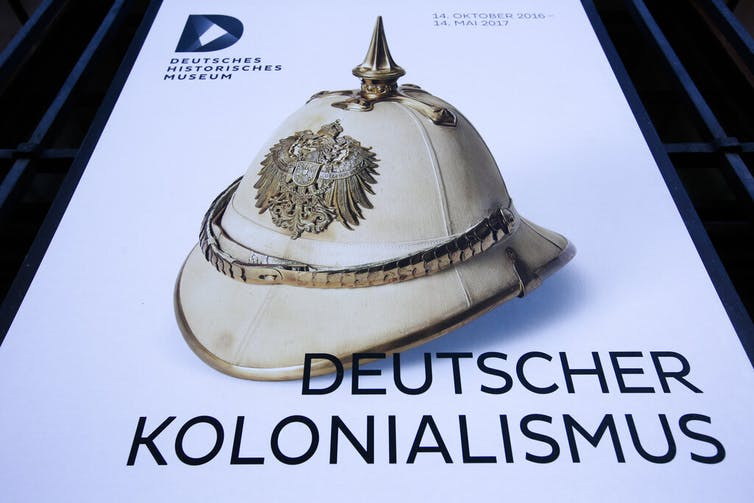 A poster for the exhibition 'German Colonialism' with a historic German spiked helmet displayed outside the German Historic Museum in Berlin, Friday, Jan. 6, 2017.