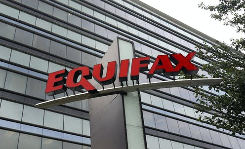 The glass façade of a large office building with a large sign mounted on a structure in front of the building bearing the name Equifax