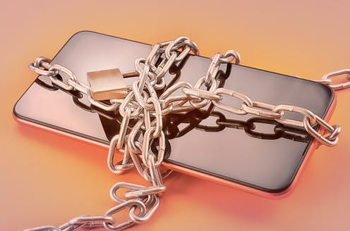A cellphone bound in a chain with a lock.