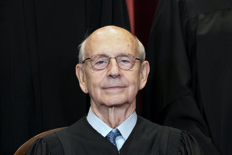 An elderly man with wire-rimmed glasses in a Supreme Court black robe.
