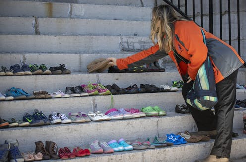 A woman places children's shoes on a stone staircase.