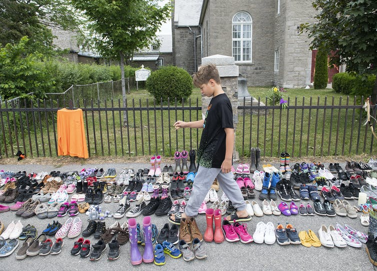 A boy puts down tobacco amid children's shoes.