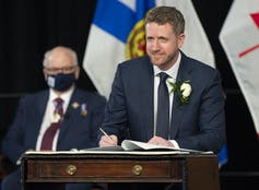 A man standing at a podium in front of the Nova Scotia flag