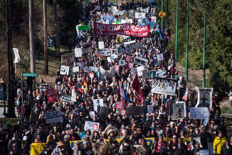 Thousands of people, including Indigenous leaders and environmentalists, march together during a protest