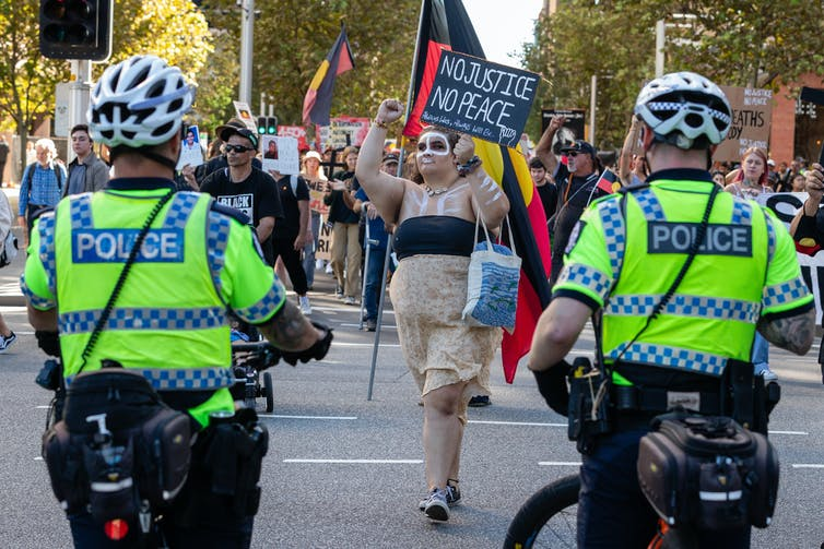 Woman protestor with placard approaches police officers at a rally.