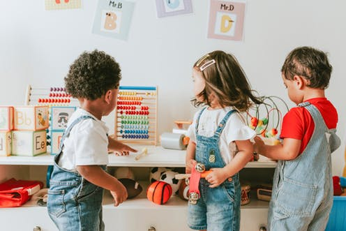 Three kids together in childcare, one pointing at an abacus.