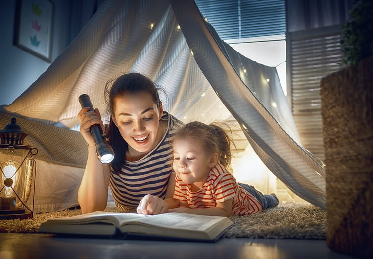 Mum reading book with daughter in a living room tent.