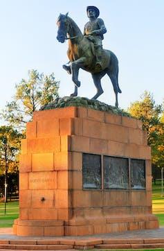 A statue of a man astride a horse, both atop a tan-bricked plinth.
