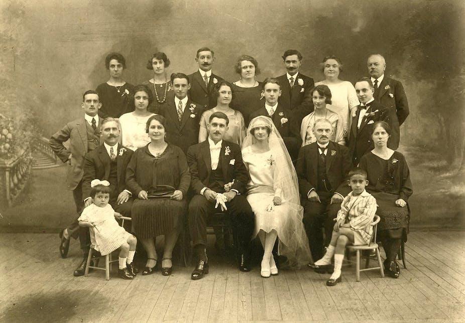 Deux mariés français posent en studio avec leurs familles, autour de 1925.