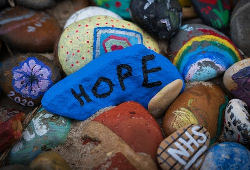 Rocks painted with rainbows, flowers and the word HOPE