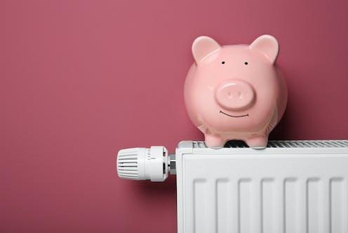 A piggy bank sits on a white radiator.
