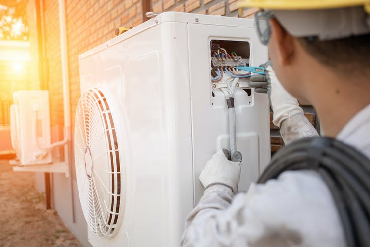 An engineer installing an air-source heat pump outside a house.