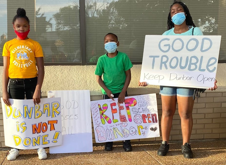 Three kids hold protest signs that read 'Keep Dunbar open'