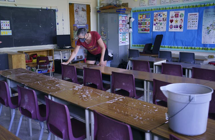 A teacher washing down desks.