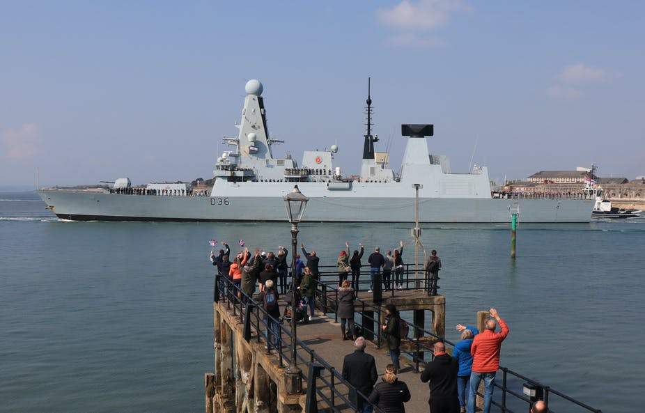 Members of public wave as the British destroyer HMS Defender leaves Portsmouth Harbour, May 2021