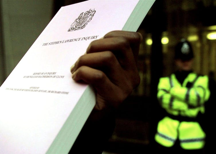 Hand holding up large document with the words STEPHEN LAWRENCE INQUIRY on the front while a police officer stands in the background
