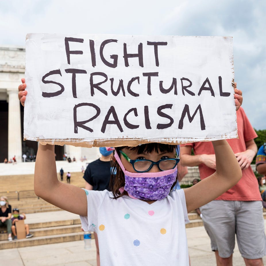 Little girl wearing glasses and a face mask holds up sign that says 'fight structural racism'