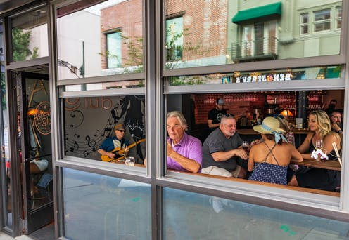 People sitting in a bar with the window open