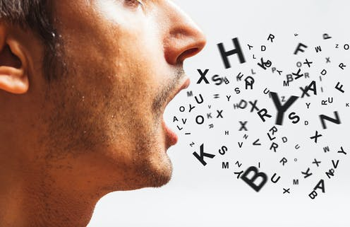 A close up, profile-view photo of a man with an assortment of letters appearing to come out of his mouth