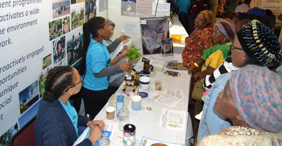 Two women in turquoise shirts standing on one side of a table full of tubs and plants talk with four women on the other side of the table, who are listening intently.