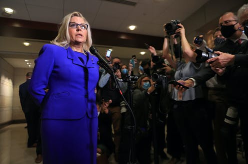 Liz Cheney, a blond woman with glasses and wearing a blue suit, talking to a large crowd of reporters