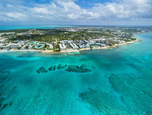 A relatively small island with luxury resorts along the short sits in the turquoise waters of the Caribbean