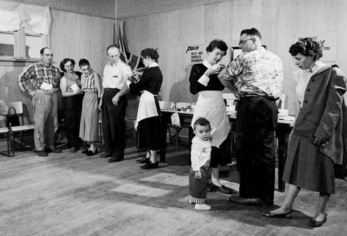 Black and white photo, nurse giving polio vaccine to man as child tugs on her apron