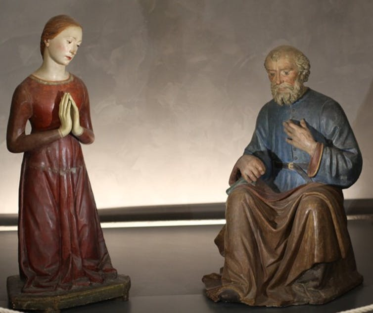 A woman in a simple red dress with hands folded in prayer next to a kneeling man.