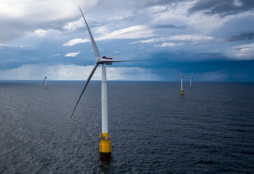 Five floating wind turbines on open ocean under a stormy sky.